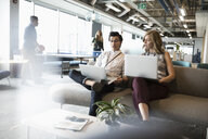 Businessman and businesswoman talking, using laptops in office lounge - HEROF11429