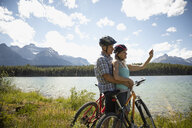 Affectionate mature couple taking selfie with camera phone, mountain biking along sunny remote lake, Alberta, Canada - HEROF11441