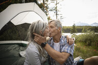 Affectionate mature couple kissing by tent at forest campsite - HEROF11444