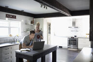 Couple using laptop in kitchen - HEROF11471
