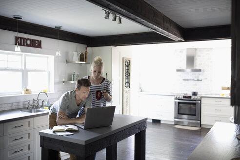Couple using laptop in kitchen - HEROF11471