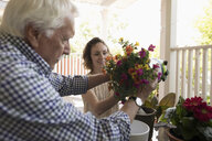 Daughter helping senior father planting flowers on porch - HEROF11480