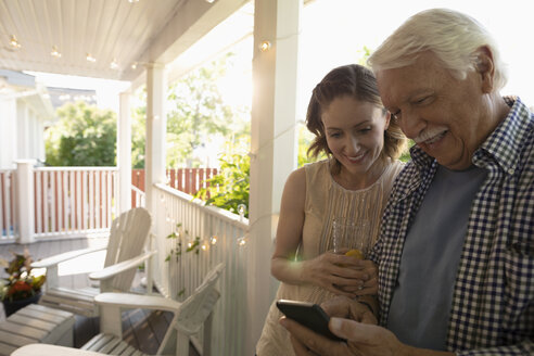Daughter watching senior father using smart phone on porch - HEROF11486