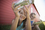 Curious girl with insect jar on rural farm - HEROF11561