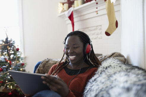 Happy young woman with headphones watching movie on digital tablet in Christmas living room - HEROF11621