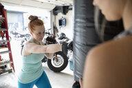 Focused woman boxing at punching bag in garage - HEROF11696