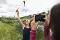 Girl with camera phone photographing playful friend fishing - HEROF11729