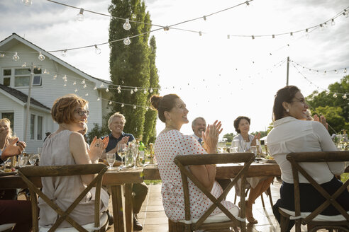 Friends clapping, celebrating at garden party table - HEROF11744