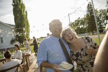 Happy couple celebrating anniversary, eating cake at garden party - HEROF11750