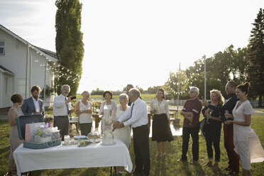 Friends watching senior bride and groom cutting wedding cake at rural wedding party - HEROF11753