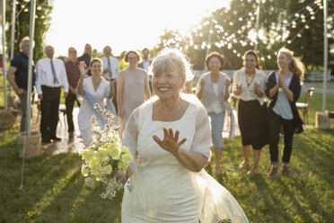 Happy senior bride throwing bouquet for cheering women in rural yard - HEROF11756