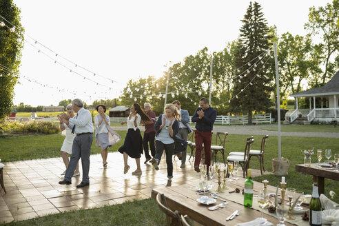 Friends dancing with senior bride and groom at wedding reception in rural garden - HEROF11759