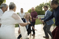 Friends dancing with senior bride and groom at wedding reception - HEROF11762