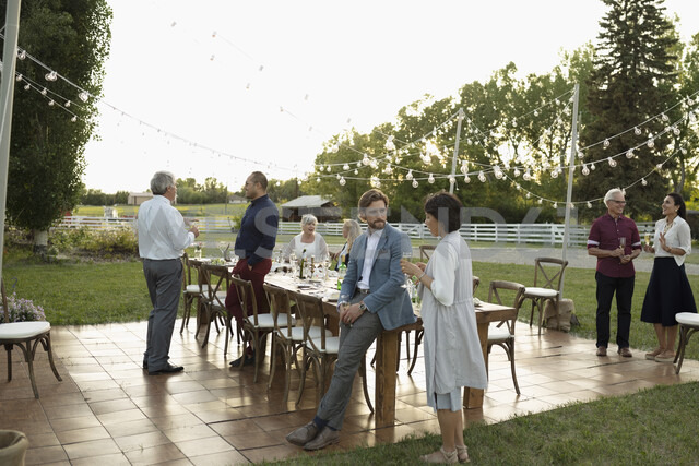 Friends talking and drinking champagne at wedding reception in rural garden - HEROF11765 - Hero Images/Westend61
