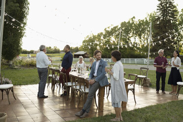 Friends talking and drinking champagne at wedding reception in rural garden - HEROF11765
