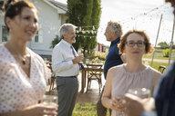 Friends talking, drinking wine at wedding reception in sunny rural garden - HEROF11774