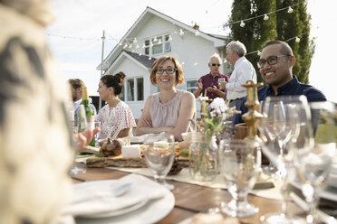 Friends enjoying wedding reception lunch at rural table - HEROF11777