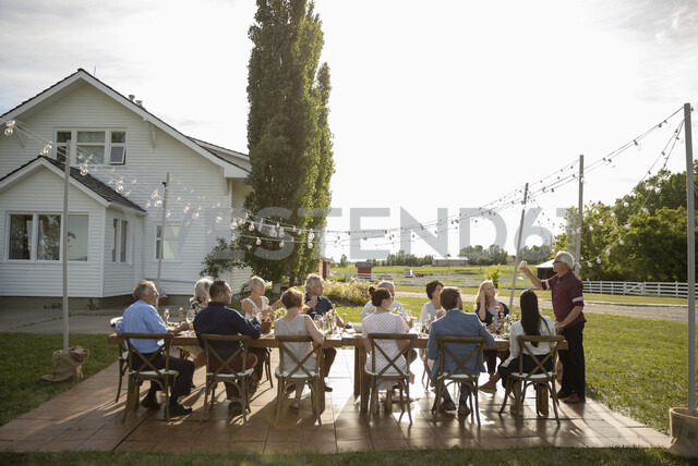 Man celebrating, toasting friends at sunny rural garden party table - HEROF11780 - Hero Images/Westend61