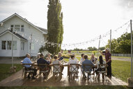 Man celebrating, toasting friends at sunny rural garden party table - HEROF11780
