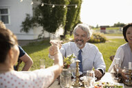 Man and woman celebrating, toasting wine glasses at sunny garden party lunch - HEROF11783