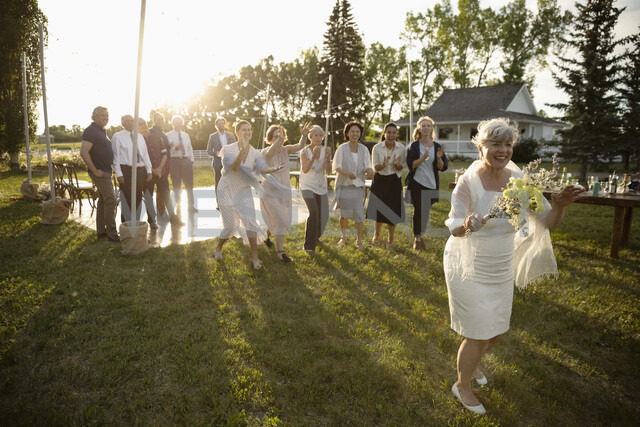 Happy senior bride preparing to throw bouquet in sunny rural garden - HEROF11798 - Hero Images/Westend61