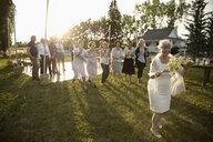 Happy senior bride preparing to throw bouquet in sunny rural garden - HEROF11798
