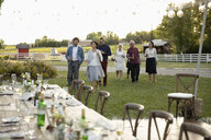 Friends walking toward wedding reception tables in rural garden - HEROF11801
