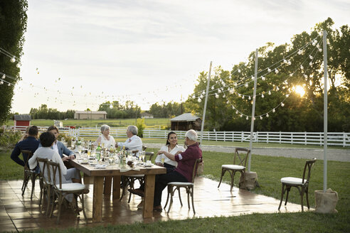 Friends talking and drinking champagne at wedding reception table in rural garden - HEROF11804