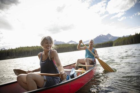 Happy mature couple canoeing on sunny lake, Alberta, Canada - HEROF11822