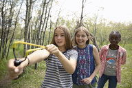 Playful tween girl friends playing with slingshot in woods - HEROF11873