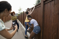 Playful teenage girl friends with camera phone climbing fence - HEROF11882