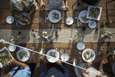 Overhead view friends enjoying lunch and wine at patio table - HEROF11891