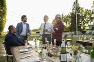 Men friends drinking champagne and talking at wedding garden party - HEROF11894