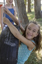 Portrait carefree girl with braces playing on tire swing - HEROF11903