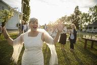 Playful senior bride preparing to throw bouquet in sunny rural garden - HEROF11915