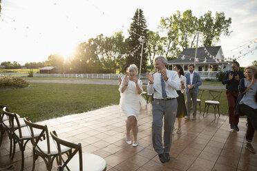 Playful senior bride and groom dancing at wedding reception in rural garden - HEROF11918