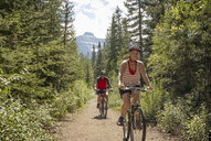 Mature couple mountain biking on sunny forest trail - HEROF11933