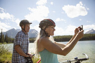 Mature couple mountain biking, taking photo with camera phone at sunny remote lake, Alberta, Canada - HEROF11939