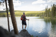 Mature man hiking with nordic walking poles, enjoying tranquil forest lake view, Alberta, Canada - HEROF11951