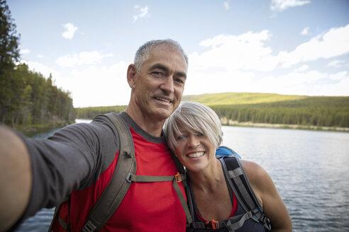 Portrait affectionate, happy mature couple taking selfie at lakeside, Alberta, Canada - HEROF11954