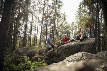 Mature couples taking a break from hiking, resting on forest rock - HEROF11960