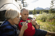 Mature couple drinking hot coffee at sunny campsite - HEROF11966