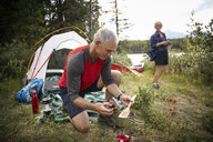Mature couple camping, cooking at forest campsite - HEROF11969