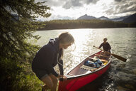 Mature women canoeing on sunny, tranquil lake, Alberta, Canada - HEROF11975