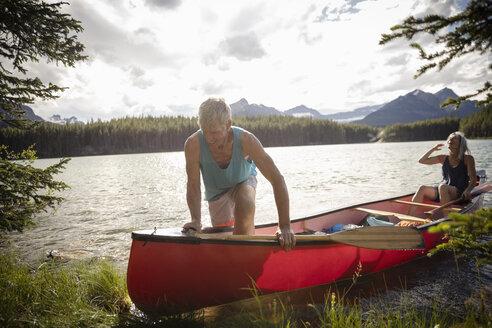 Mature couple canoeing at sunny, tranquil lake, Alberta, Canada - HEROF11978