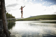 Mature woman on diving board above tranquil lake, Alberta, Canada - HEROF11984