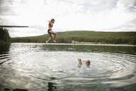 Mature woman jumping off diving board into lake, Alberta, Canada - HEROF11993