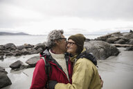 Affectionate active senior couple hugging on rugged beach - HEROF11999