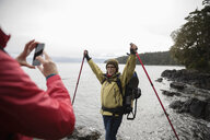 Active senior woman photographing friend backpacking along ocean - HEROF12014