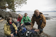 Active senior couple friends backpacking, resting on rugged beach - HEROF12020